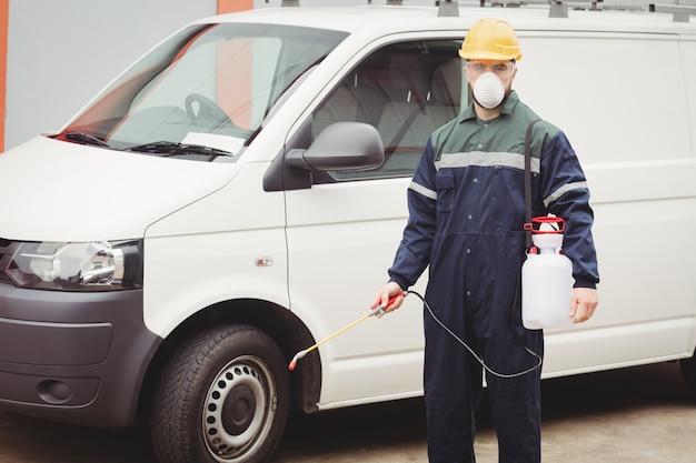 Разнорабочий с инсектицидом стоит перед своим фургоном