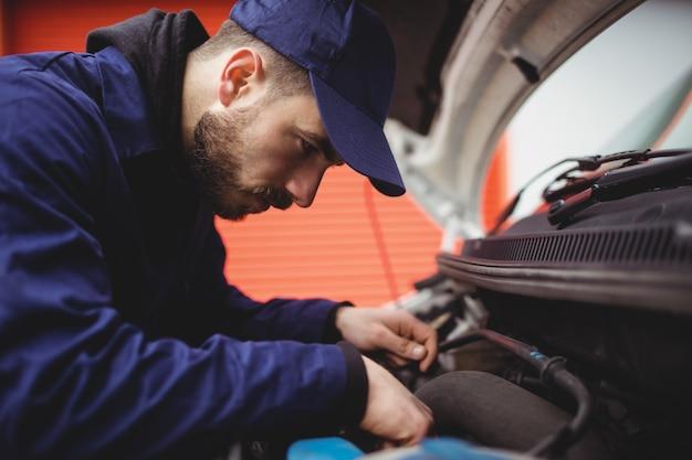 バンのエンジンを修理するメカニック