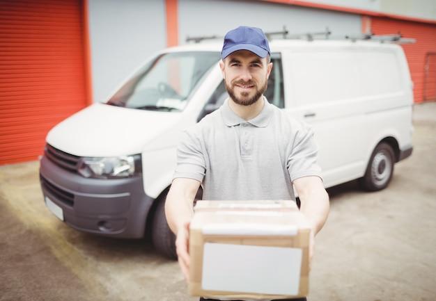 Доставка человек держит пакет перед своим фургоном