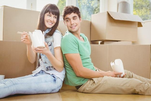 Молодая пара сидит на полу и ест лапшу в своем новом доме