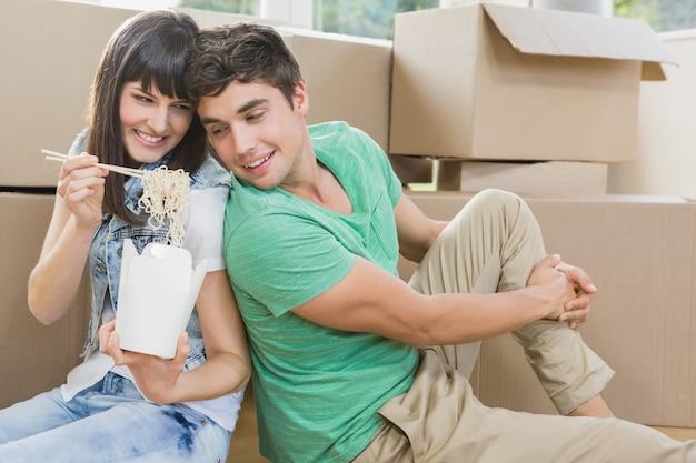 若いカップルが床に座って、彼らの新しい家で麺を食べる