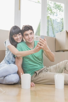 彼らの新しい家で携帯電話を使用して若いカップル