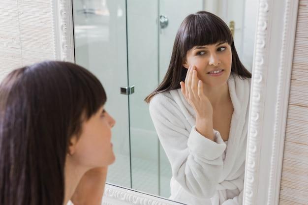 鏡で見ている白いバスローブを着ている美しい若い女性