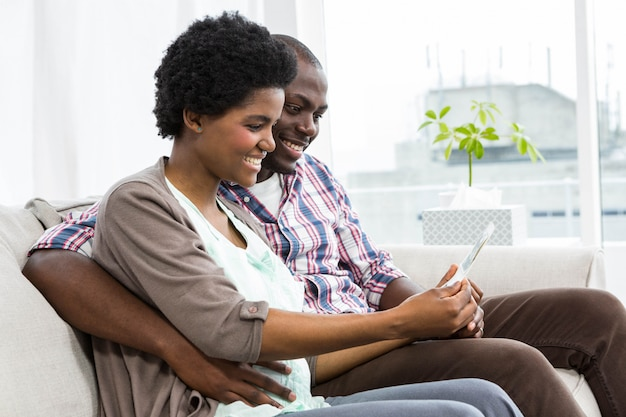 妊娠中のカップルがソファに座って、自宅でデジタルタブレットを使用して
