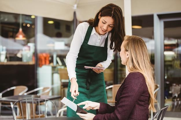 Улыбающаяся официантка, принимающая заказ в кафе