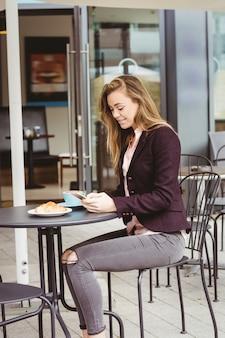 カフェで彼女のスマートフォンを使用して女性