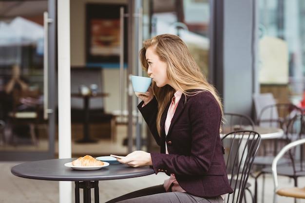 カフェで一杯のコーヒーを飲む女性