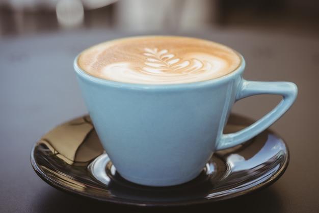 コーヒーショップで木製のテーブルの上のコーヒーアートとカプチーノのカップ