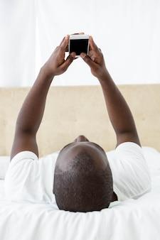 ベッドとテキストメッセージを自宅で携帯電話に横たわっている男