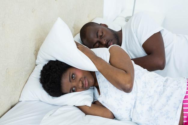 Беременная женщина закрывает уши, а мужчина храпит