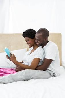 妊娠中のカップルが自宅のベッドで本を読んで