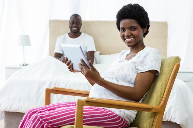椅子とバックグラウンドでベッドの上に座っている男にデジタルタブレットを使用して妊娠中の女性の肖像画