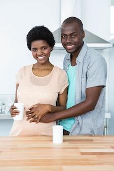 キッチンでコーヒーを飲みながらお互いを受け入れて妊娠中のカップルの肖像画