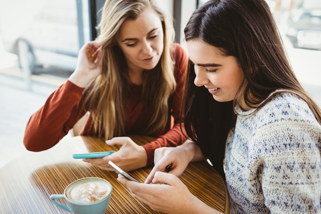 スマートフォンを使用して、コーヒーショップでコーヒーを飲んでいる友人