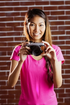 レンガの壁にカメラで写真を撮る笑顔のアジア女性
