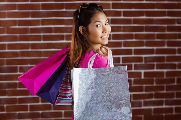 レンガの壁に買い物袋を持つアジア女性の笑みを浮かべてください。