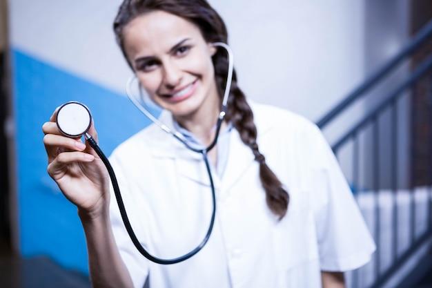 病院で聴診器を示す女性医師の肖像画