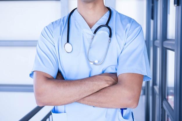 腕を組んで病院に立っている男性医師