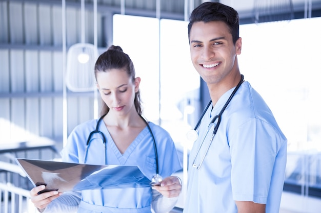 Усмехаясь доктор осматривая отчет о луча топора с его коллегой в больнице