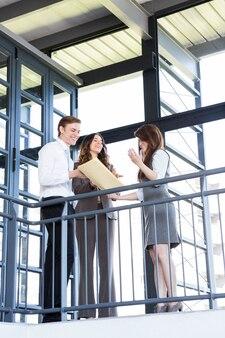 Бизнесмены, глядя на документы в офисе