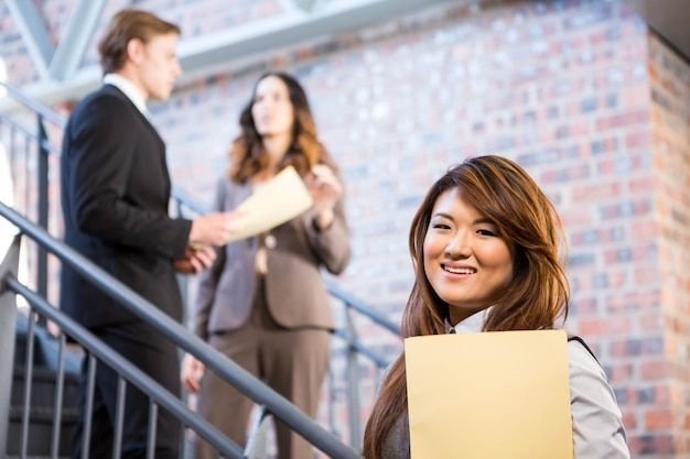 Коммерсантка стоя около лестницы с документами в офисе