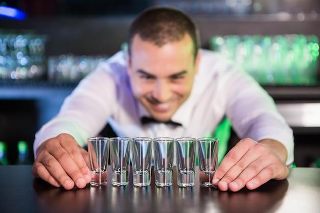 バーのバーカウンターにショットグラスを一列に配置するバーテンダー