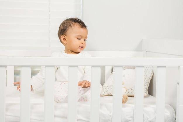 ベビーベッドの上に座ってかわいい赤ちゃん