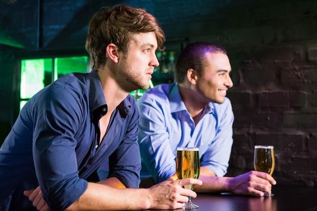 二人の男がバーのカウンターでビールを飲みながら笑ってバー
