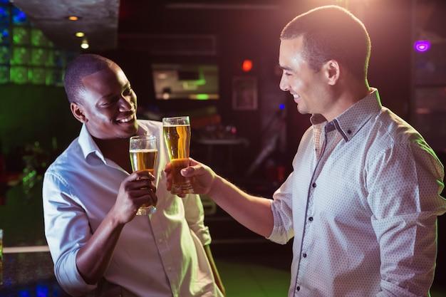 二人の男がビールのグラスで乾杯バーで