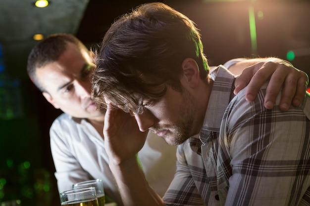 Человек утешает своего подавленного друга в баре