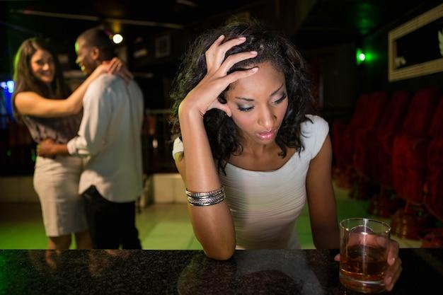バーカウンターと彼女の後ろに踊るカップルに座っている不幸な女性バー