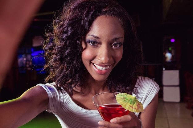 Портрет молодой женщины с коктейлем в баре