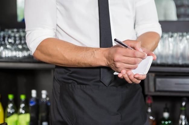 Официант записывает заказ в баре
