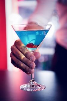 バーで青いマティーニを提供するバーテンダー
