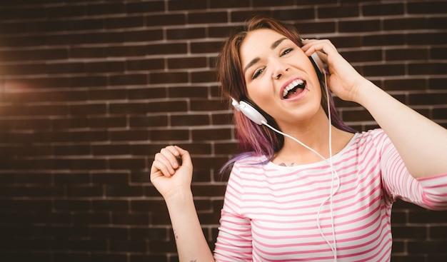 ヘッドフォンで音楽を聞いて笑顔の女性の肖像画