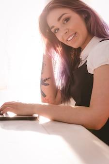 オフィスでラップトップに取り組んで笑顔のエグゼクティブ