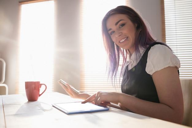 オフィスでデジタルタブレットと携帯電話を使用してエグゼクティブを笑顔