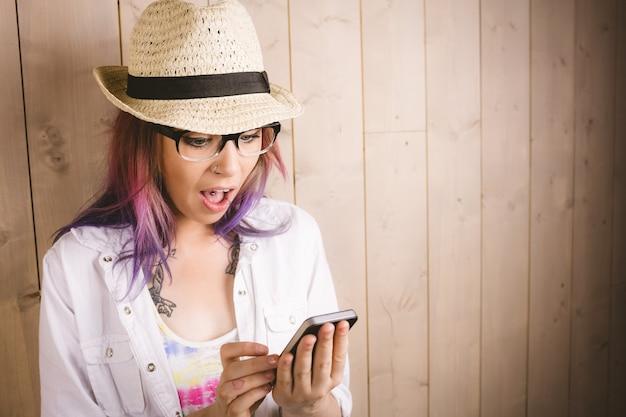 Удивленная женщина с помощью мобильного телефона