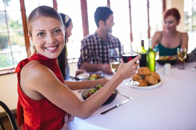 レストランでワイングラスを保持している女性