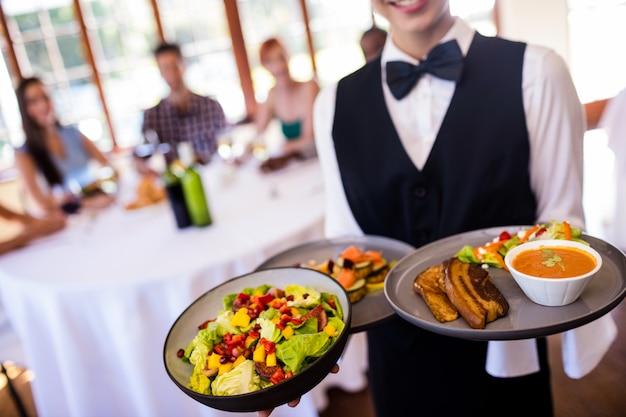 レストランで皿に食べ物を保持しているウェイトレス