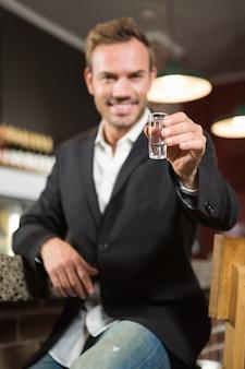 アルコールのショットを持っているハンサムな男