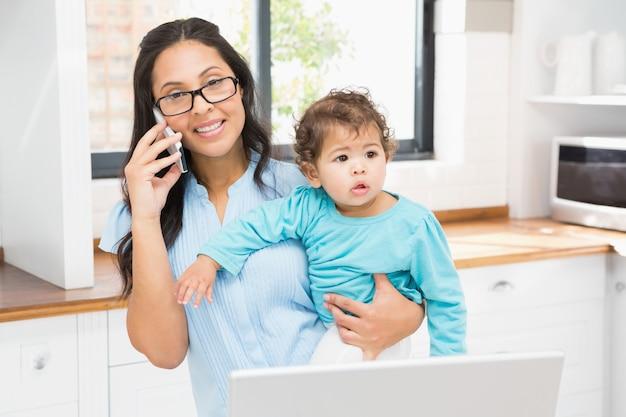 Улыбающаяся брюнетка, держащая ее ребенка и использующая ноутбук на телефонном звонке на кухне