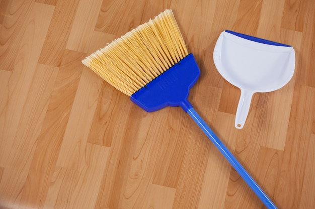 Подметающая метла и совок на деревянном полу