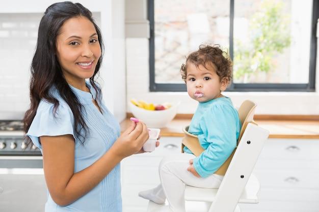 Счастливая брюнетка кормит своего ребенка на кухне