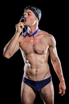 水泳選手が彼の金目たるにキス