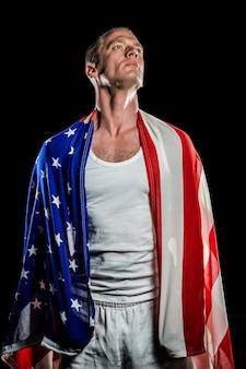 Спортсмен с американским флагом, обернутым вокруг его тела