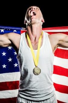 Спортсмен позирует с золотой медалью после победы