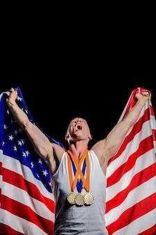 Спортсмен позирует с золотыми медалями после победы