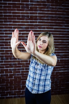 Довольно блондинка, глядя через ее руки