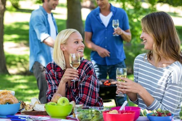 ワインとバーベキューでピクニックを持っている友人